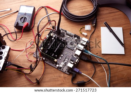 Electronic project or prototype making. Bare computer circuit board hooked up on a work table.    - stock photo
