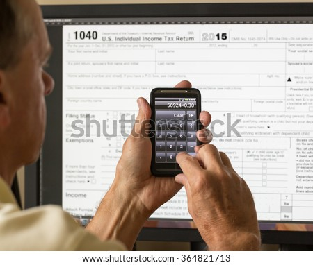 Electronic tax form 1040 for 2015 for US individual return on screen with smartphone calculator - stock photo