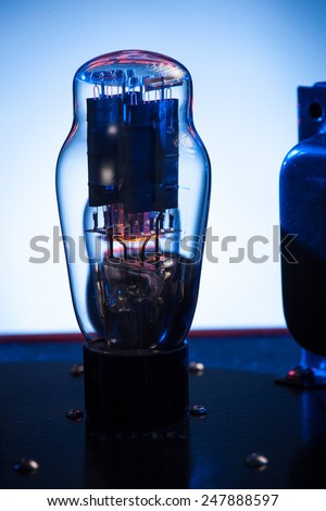 Electronic vacuum tube,in a hi fi amplifier with white and blue background - stock photo