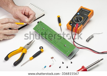 Electronics engineer checking the value of a resister component - stock photo