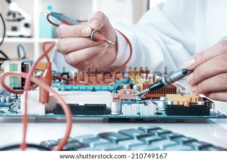 Electronics repair service, hands of female tech fixes an electronic circuit - stock photo