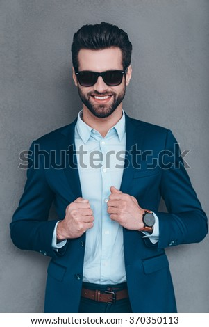 Elegance and masculinity. Cheerful young handsome man in sunglasses keeping hand on his jacket and looking at camera with smile while standing against grey background - stock photo
