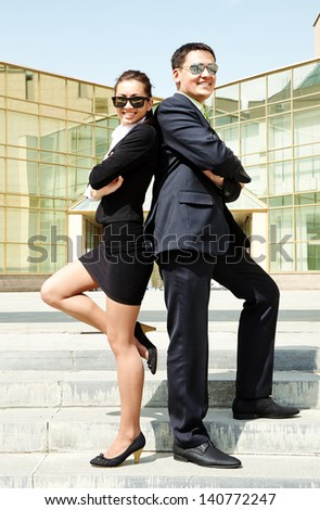 Elegance businesspeople in sunglasses standing back to back near office - stock photo