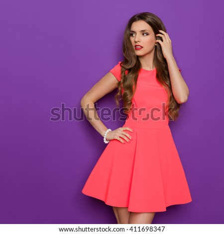 Elegance young woman in pink mini dress posing with hand on hip and looking away. Three quarter length studio shot on purple background. - stock photo