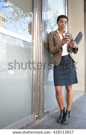 Elegant african american business woman leaning on a reflective glass office building outdoors, using a smart phone to work, city exterior. Professional black woman using technology, sunny exterior. - stock photo