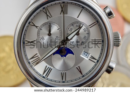 Elegant and beautiful wristwatch on a coins background  - stock photo