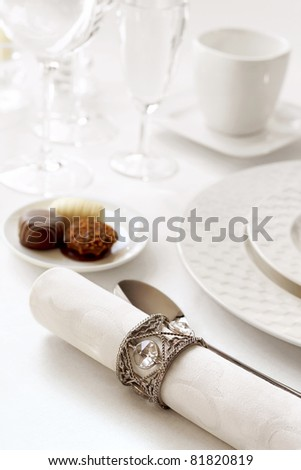 Elegant and chic restaurant table setting with chocolates - stock photo