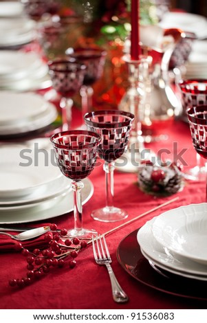 Elegant and decorated table setting with white dishes over a red tablecloth. Silver cutlery and red glasses - stock photo