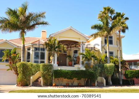 Elegant and eclectic, this home has beautiful curb appeal as the palm trees and bushes surround the modern victorian-spanish home. Entryway is on the second level with a large porch as a landing. - stock photo