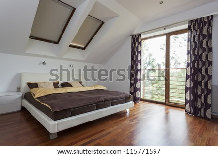 Elegant and modern bedroom with a balcony - stock photo