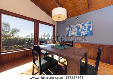Elegant and modern Dining area in craftsman home with large window and daylight - stock photo