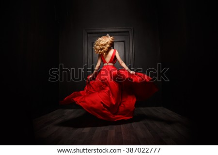 Elegant and sexy woman in the red evening fluttering dress is capture in move, running away from the ceremony (the 	 ball), the wooden door is on the background - stock photo