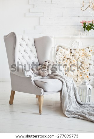Elegant arm-chair with knitted blanket on it. Comfort interior in white color - stock photo