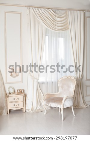 Elegant arm-chair with near a window. Luxury interior in white colors - stock photo