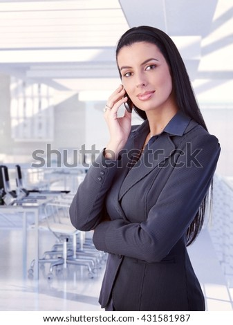 Elegant attractive brunette caucasian businesswoman with mobile phone standing at classy business office. Smiling, looking at camera, copyspace, suit. - stock photo