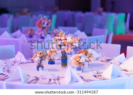 Elegant banquet table prepared for conference or party and decorated flowers for guests.  - stock photo