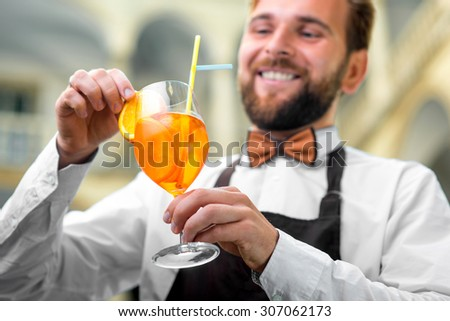 Elegant barman in uniform with butterfly making cocktail with sparkling wine, aperol and orange - stock photo