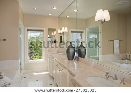 Elegant bathroom with marble, double sink, glass door shower, bath tub and super large mirror.  - stock photo