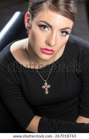 Elegant beautiful woman in a black cocktail dress and long gloves wearing cross necklace - stock photo