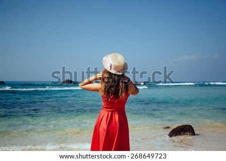 Elegant Beautiful Woman in Red Dress and straw hat on the Beach. Young girl on sand beach with palm trees. ocean paradise. View of model from back - stock photo