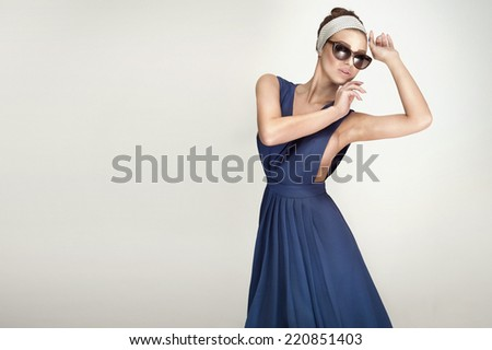Elegant beautiful woman wearing fashionable dress and sunglasses posing, studio shot - stock photo