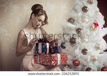 elegant beautiful woman with hair-style sitting near decorated tree with some Christmas presents. Xmas concept.  - stock photo