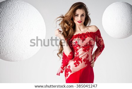 Elegant beautiful woman with long curly hair and glamour makeup posing in evening red dress, looking at camera. Studio shot. - stock photo