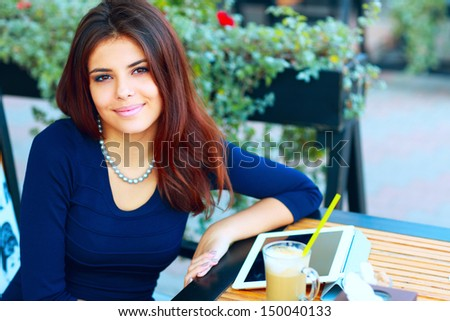 Elegant beautiful woman with tablet computer drinking coffee at cafe - stock photo
