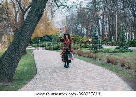 Elegant beautiful young woman in a vintage hat burgundy color and the old English coat walks with suitcase like an American flag with Stars and Stripes, extravagant - stock photo