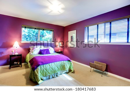 Elegant bedroom with beige carpet floor and contrast color bright purple walls. Green and purple bedding blend perfectly with red wall - stock photo