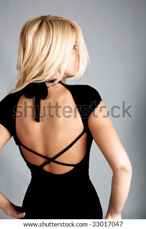 elegant blond woman in black dress, back view, studio shot - stock photo