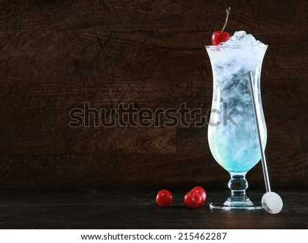Elegant blue curacao cocktail with ice and a swizzle-stick garnished with fresh cherries on a dark background with copyspace for your Christmas message or tropical vacation text - stock photo