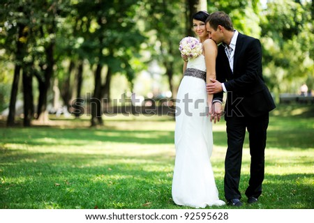 Elegant bride and groom posing together outdoors on a wedding day - stock photo