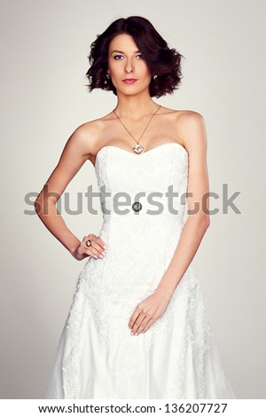 elegant bride in white dress over grey background - stock photo