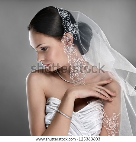 elegant bride with diamond jewellery and veil on grey background - stock photo