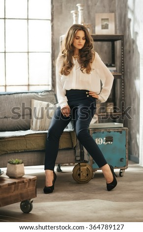 Elegant brunet woman in stylish outfit sitting on couch in loft apartment - stock photo