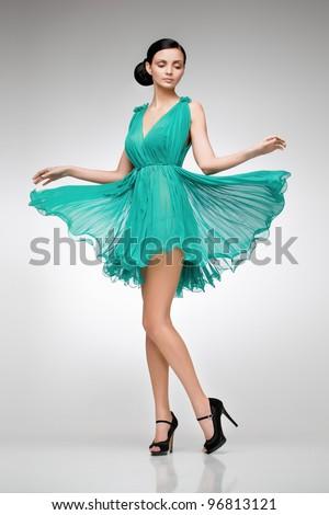 elegant brunette in green dress posing in the studio - stock photo