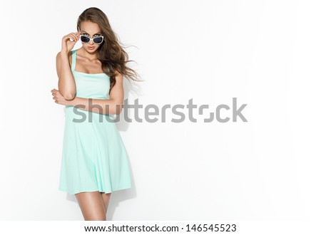 elegant brunette in mint dress and sunglasses posing in the studio  - stock photo