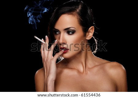 Elegant brunette woman smoking a cigarette on black background - stock photo