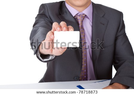 Elegant Business man dressed in suit, shirt and tie, handing a blank business card, isolated over white background. Sitting at the office desk. Meeting concept - stock photo