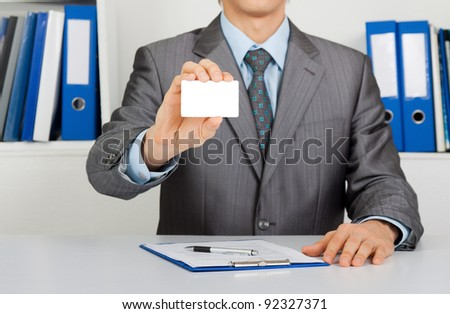 Elegant Business man handing a blank business card, dressed in suit, shirt and tie, Sitting at the office desk. Meeting concept - stock photo