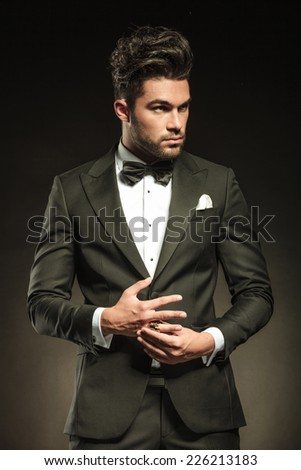 Elegant business man looking away from the camera while playing with his ring. On black studio background. - stock photo