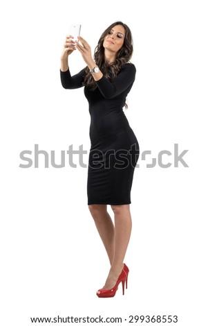 Elegant business woman in black dress talking selfie with cellphone. Full body length portrait isolated over white studio background.  - stock photo
