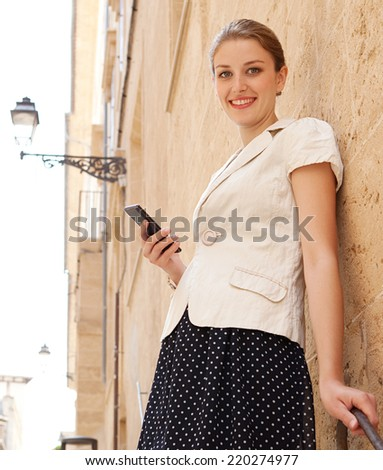 Elegant business woman standing in a classic city with textured stone buildings and walls, holding a high technology smartphone in her hand, smiling at the camera outdoors. People and technology. - stock photo