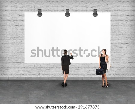 Elegant business women standing and looking at blank white billboard. Copy-space for advertise. - stock photo