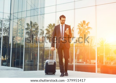 Elegant businessman checking e-mail on mobile phone while walking with suitcase outside airport, experienced male employer using cell telephone while waiting for taxi car outdoors before work travel - stock photo