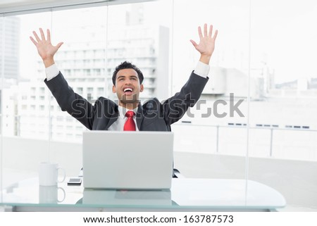 Elegant businessman cheering with raised hands in front of laptop at office desk - stock photo