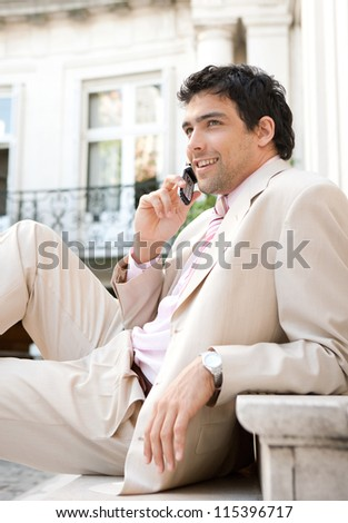 Elegant businessman having a conversation on a cell phone while sitting at an office building entrance, smiling. - stock photo