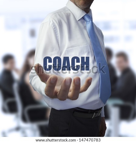 Elegant businessman holding the word coach in front of a business team - stock photo