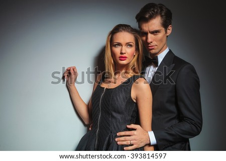 elegant businessman in black suit looking at the camera while embracing woman from behind. woman raise hand while looking away in gray studio background - stock photo